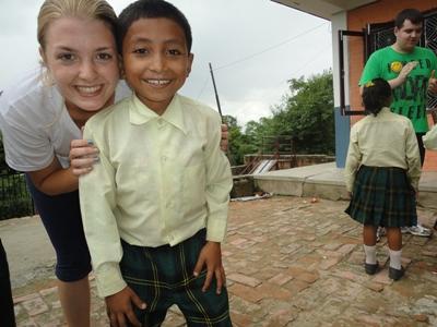교실밖에서 네팔 아이들과 포즈를 취하는 여성 봉사자