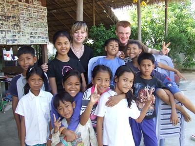 캄보디아 교육 프로젝트 봉사자들이 수업을 끝내고 교실밖에서 학생들과 포즈를 취하고 있다