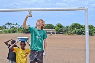 가나 아이들이 건축 프로젝트 봉사자를 도와 페인팅을 하고 있다