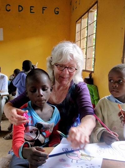 탄자니아 사회복지 프로젝트 봉사자가 어린이를 도와 함께 액티비티를 하고 있다