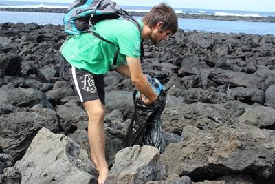 남성 봉사자가 에콰도르 해안에서 쓰레기를 줍고 있다