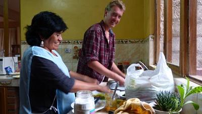 호스트 마더가 자원봉사자에게 페루 현지식을 요리하는 방법을 가르쳐주고 있다