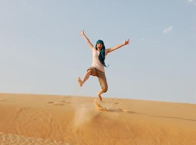 여가시간에 여행에 나선 세네갈 프로젝트 봉사자들이 사막 가운데서 점프 하고 있다
