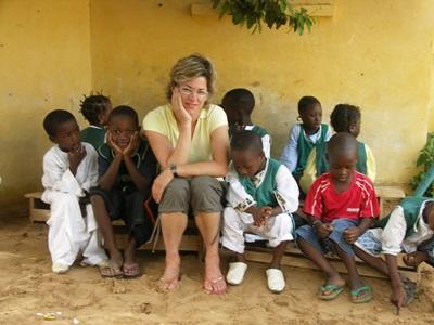 봉사자들이 세네갈 어린이들과 벤치에 앉아있다