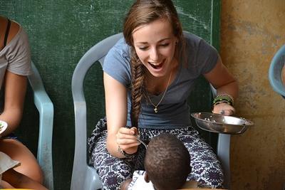 프로젝트 어브로드 자원봉사자가 토고 어린이 밥을 먹이고 있다