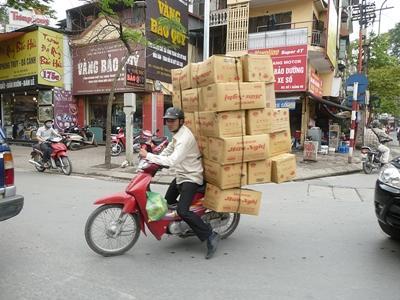 베트남 남성이 오토바이 뒤에 박스들을 싣고 가고 있다
