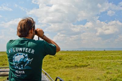 프로젝트어브로드 환경보호 봉사자가 케냐 소야삼부 국립공원에서 망원경으로 기린을 관찰한다