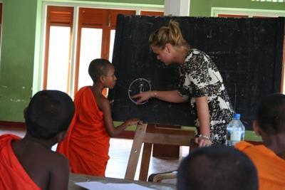 스리랑카에서 여성 봉사자가 어린 승려들에게 읽기를 지도하고 있다