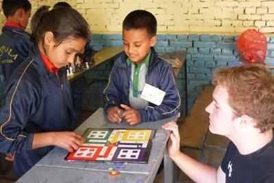 봉사자가 네팔 어린이들과 게임을 하고 있다.