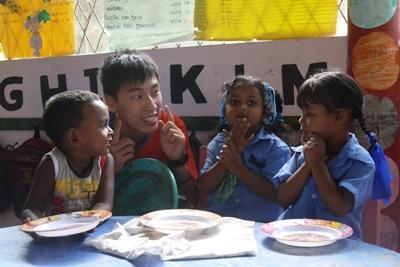 스리랑카 프로젝트 사회복지 프로젝트 봉사자가 파나두라의 활동지에서 아이들과 함께 식사시간을 기다리고 있다.