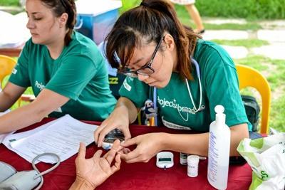 필리핀 공중 보건 프로젝트 봉사자가 주민의 혈당을 재고 있다.