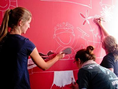 아르헨티나 사회복지 프로젝트 봉사자들이 유치원에서 벽화를 그려주고 있다.