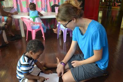 벨리즈 사회복지 프로젝트 봉사자가 어린이에게 알파벳을 가르쳐주고 있다.