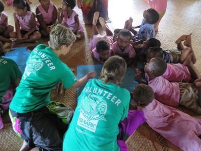 유치원 아이들과 교육 게임을 하는 봉사자들