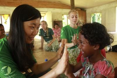 봉사자와 피지 여자 어린이가 손뼉치기 게임을 하며 놀고 있다