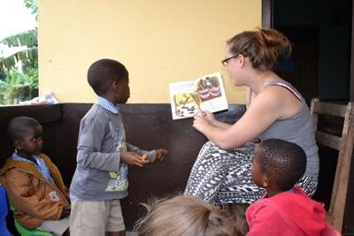 가나 사회복지 프로젝트 봉사자가 어린이드레게 이야기를 읽어주고 있다