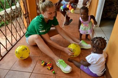 프로젝트 어브로드 자메이카 봉사자가 커뮤니티를 방문해서 어린이들과 놀아주고 있다