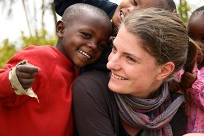 케냐 유치원에서 여성 봉사자가 어린이와 함께 웃음 짓고 있다