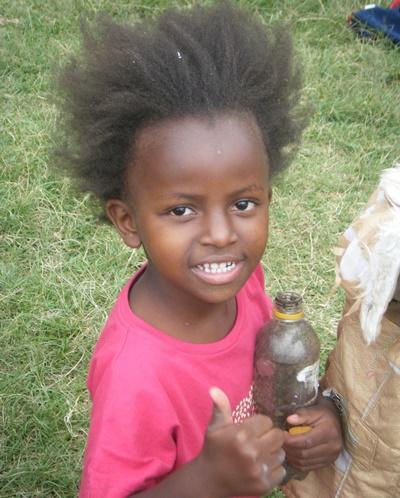 케냐 남자 어린이가 사회복지 프로젝트 봉사자를 해야 엄지손가락을 치켜 세우고 있다