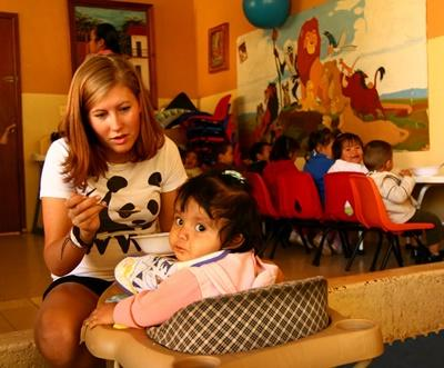 멕시코 사회복지 프로젝트 봉사자가 어린이에게 밥을 먹이고 있다