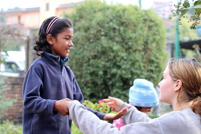 네팔 어린이가 봉사자와 함께 손뼉치기 게임을 하고 있다