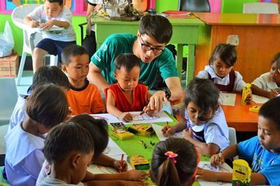필리핀 케어 프로젝트 봉사자가 어린이들의 액티비티를 돕고 있다