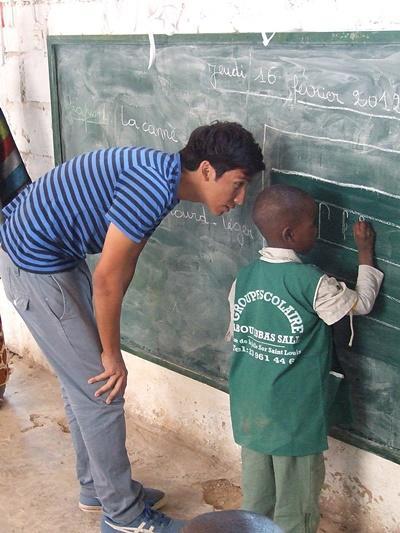 세네갈 프로젝트 봉사자가 교실에서 칠판에 적힌 문제를 푸는 학생을 돕고 있다