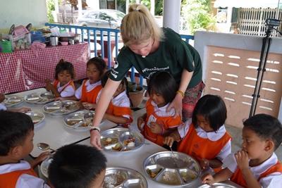 사회복지 프로젝트 봉사자가 점심시간에 어린이들을 돌보고 있다