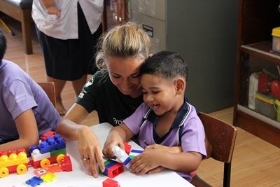 태국 어린이가 사회복지 프로젝트 봉사자와 함께 블록쌓기를 하고있다