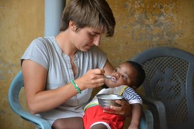 사회복지 프로젝트 봉사자가 토고 유아에게 우유를 먹이고 있다