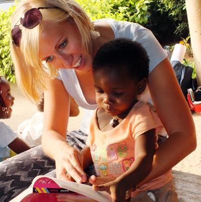 여성 봉사자가 토고 어린이의 읽기연습을 돕고 있다