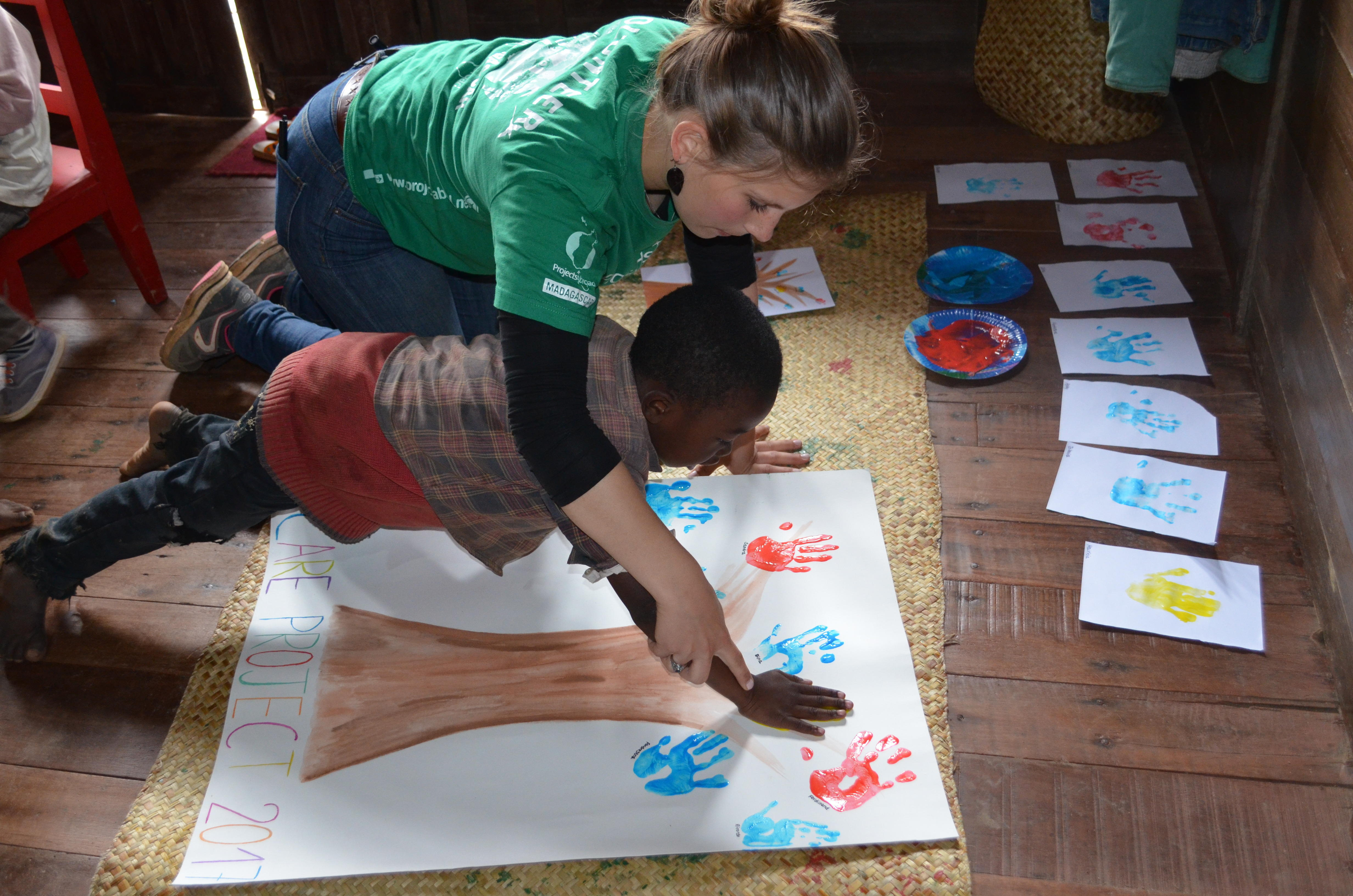 마다가스카르 케어센터에서 케어 프로젝트 봉사자가 어린이를 도와 손도장을 찍어 그림을 완성하고 있다.