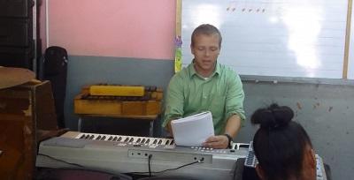자메이카에서 음악 프로젝트에서 봉사자가 피아노를 가르치고 있다
