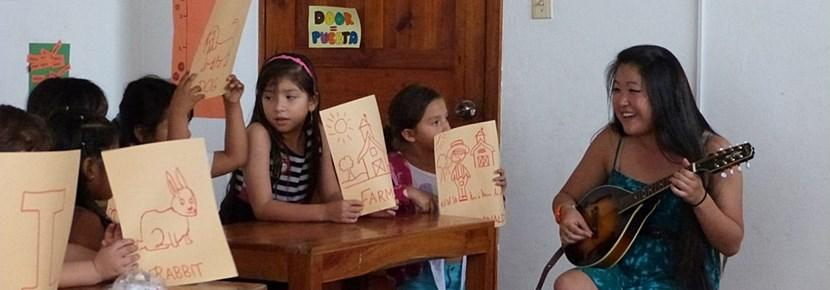 학교교육봉사에서 아이들에게 음악 기타를 가르치는 공연예술 봉사자