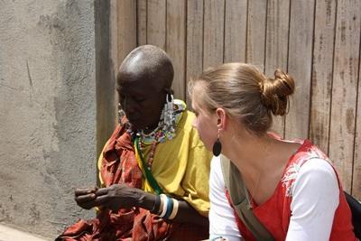 아프리카 탄자니아에서 마사이 부족 여성과 봉사자가 수공예를 하고 있다