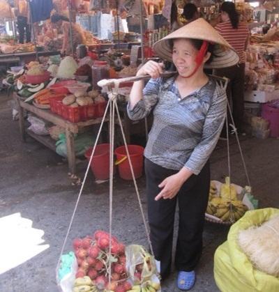 베트남 전통 시장에서 지역주민 여성이 밀짚보자를 쓰고 있다