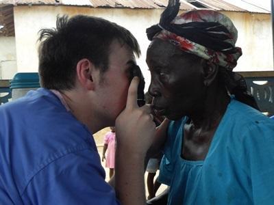 현지 여성 노인의 시력을 검사하는 의료선택 인턴 봉사자