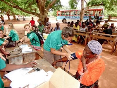 자메이카에서 환자의 혈압을 재고 있는 의료선택 인턴