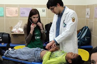멕시코에서 환자진료하는 의사를 돕는 공중보건 봉사자