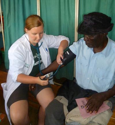 탄자니아에서 중년여성의 혈압을 체크하는 의료인턴