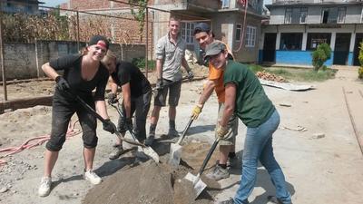 네팔 건축 프로젝트 고등학생 봉사자들이 함께 시멘트를 섞고 있다.