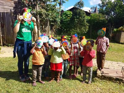 프로젝트어브로드 케어 봉사자가 마다가스카르 어린이들과 함께 가면을 만들어 자랑하고 있다