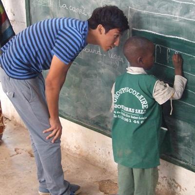 세네갈에서 사회복지 및 지역사회 프로젝트에 참가한 청소년 봉사자들이 어린 학생의 공부를 가르쳐주고 있다