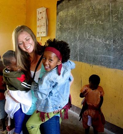 탄자니아에서 사회복지 및 지역사회 봉사활동 참가자가 아이들을 돌봐주고 있다