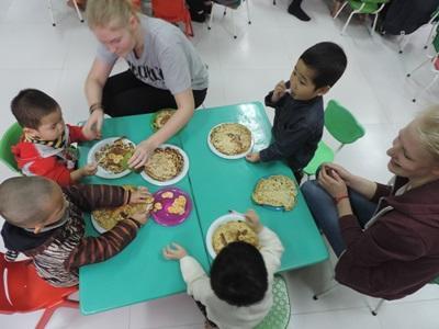 베트남 어린이들이 두명이 자원봉사자와 함께 식사를 하고 있다