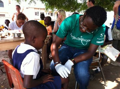 가나 지역사회의 대외의료봉사 메디컬 아웃리치활동에 참가한 봉사자가 아이를 돌보고 있다