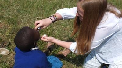 케냐의 의료 프로젝트 봉사자가 아이들을 치료하고 있다
