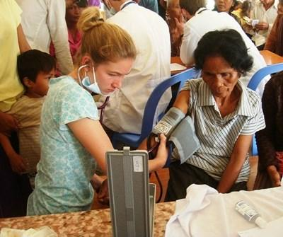 Teen volunteer in Cambodia checks an elderly woman's blood pressure on a Medicine project
