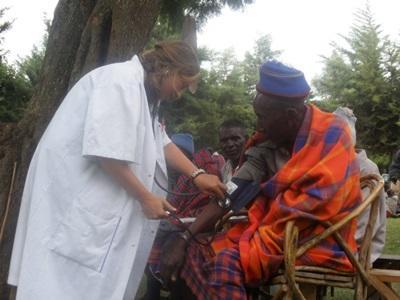 청소년 봉사자가 탄자니아의 공중보건 프로젝트에서 노인 여성을 돕고 있다