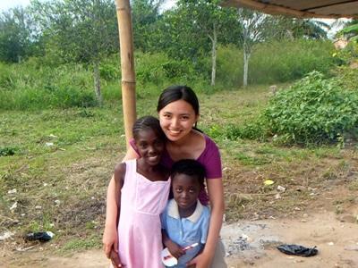 가나에서 아시아 봉사자가 현지 소녀들과 사진을 찍고 있다